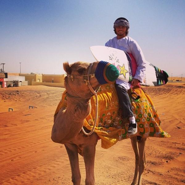 Matt Meola riding a camel on his surf trip to Wadi Adventure Wave Pool